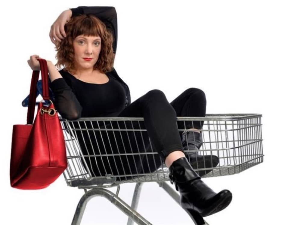 Comedian Sophie Willan Branded sat in shopping trolley with red bag