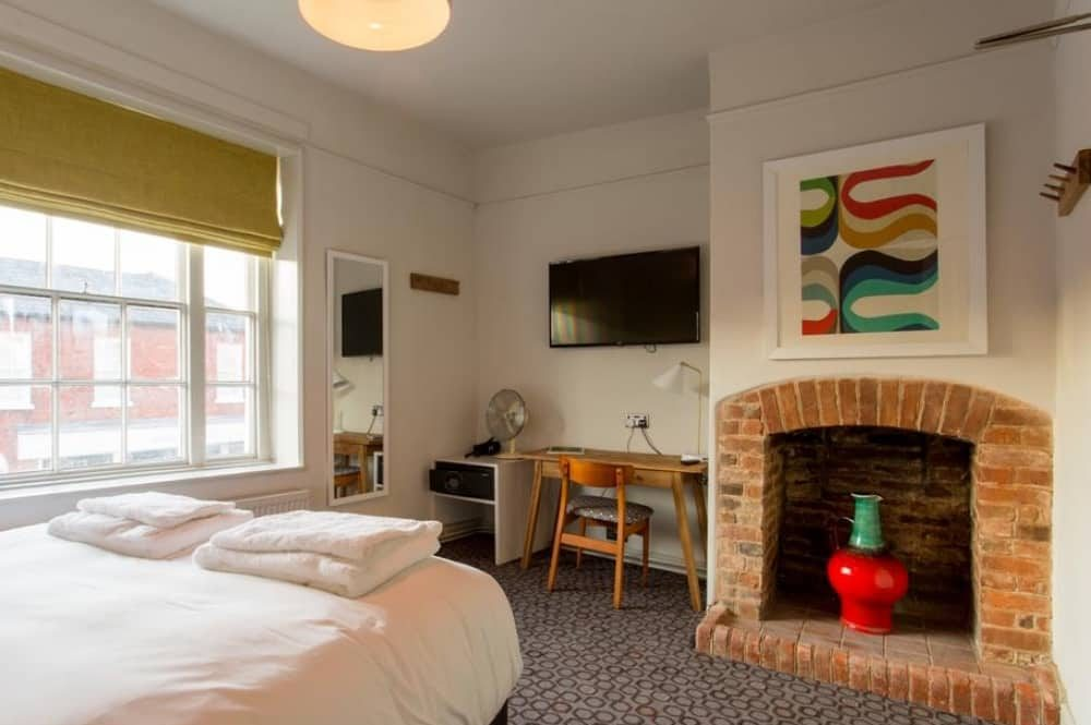 The Dolphin Pub Newbury Berkshire brick fireplace, modern art and mid century furniture in cool boutique room
