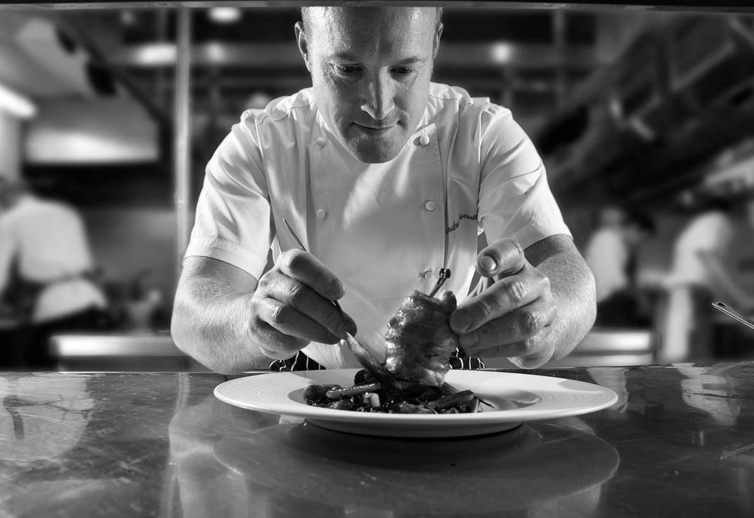 Cliveden House Hotel Taplow Berkshire Chef Andre Garrett plating up food in kitchen black and white