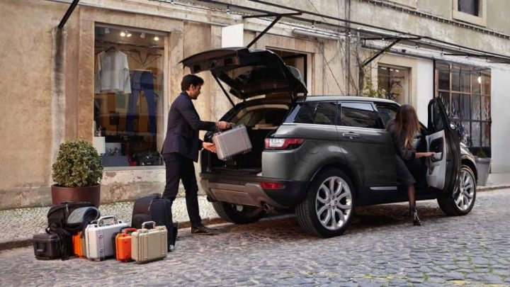 Range Rover Evoque woman getting in drivers seat man loading the bags and shopping