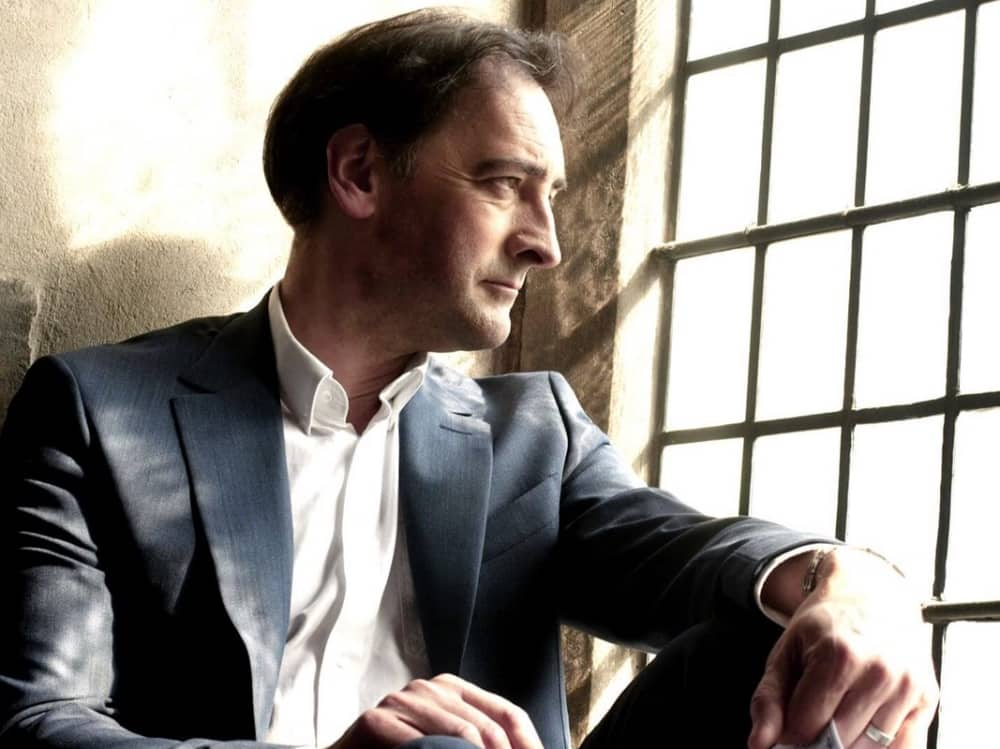British impressionist Alistair McGowan staring out of a window in a suit