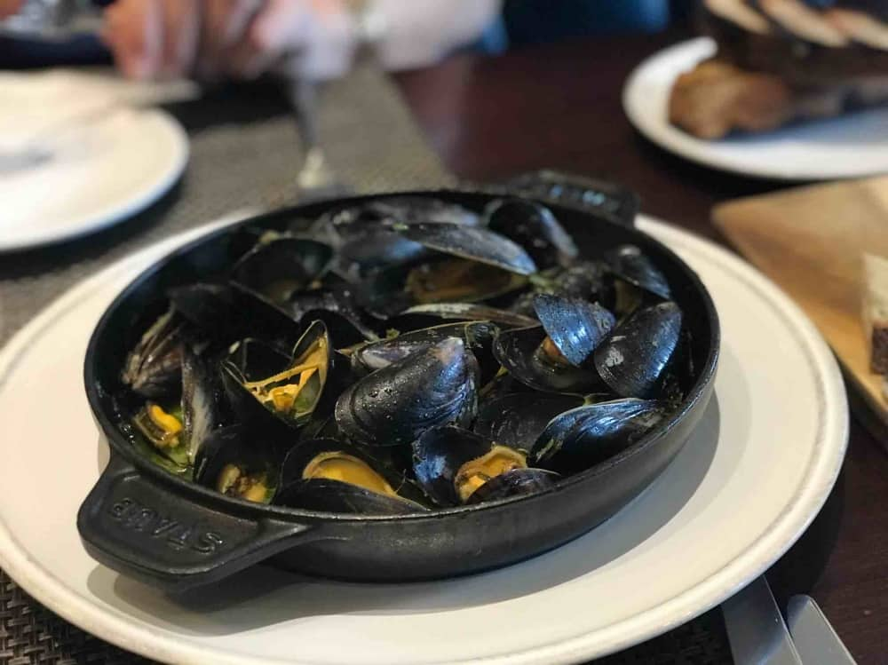 Astor Grill Cliveden House Hotel Black Staub dish on what plate full off mussels in herb and garlic butter