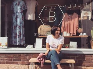 B The Lifestyle Shop Newbury Berkshire independent fashion and homeware scandi style boutique founder and owner Emma sat on a bench outside the shop window
