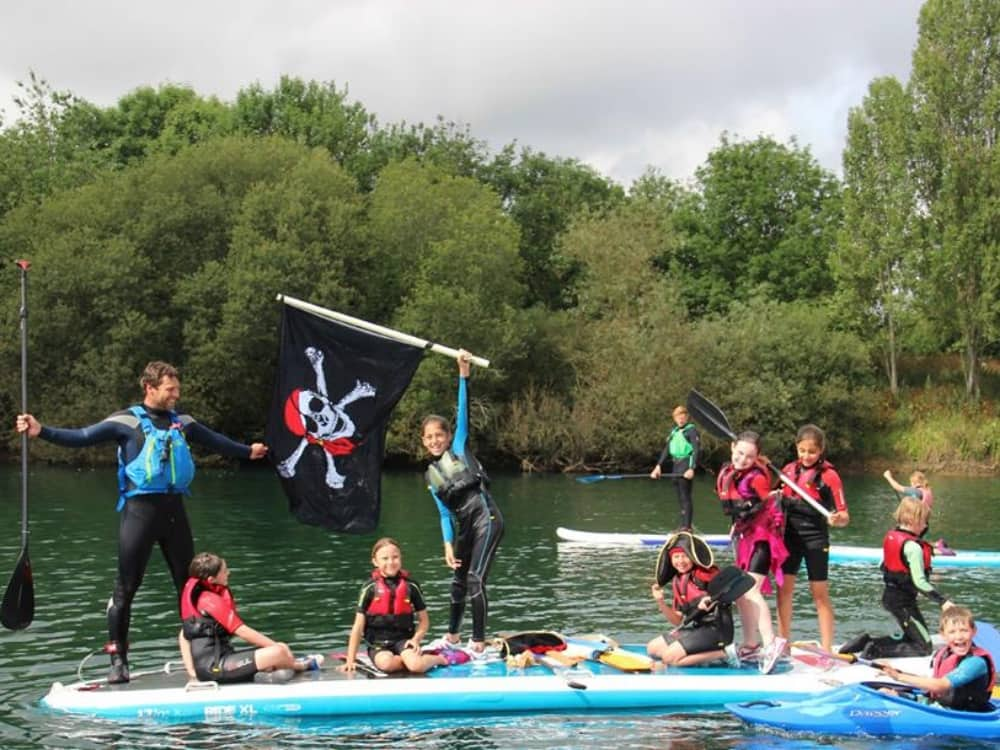 Bray Lake Watersports kids paddle boarding with jolly roger flag