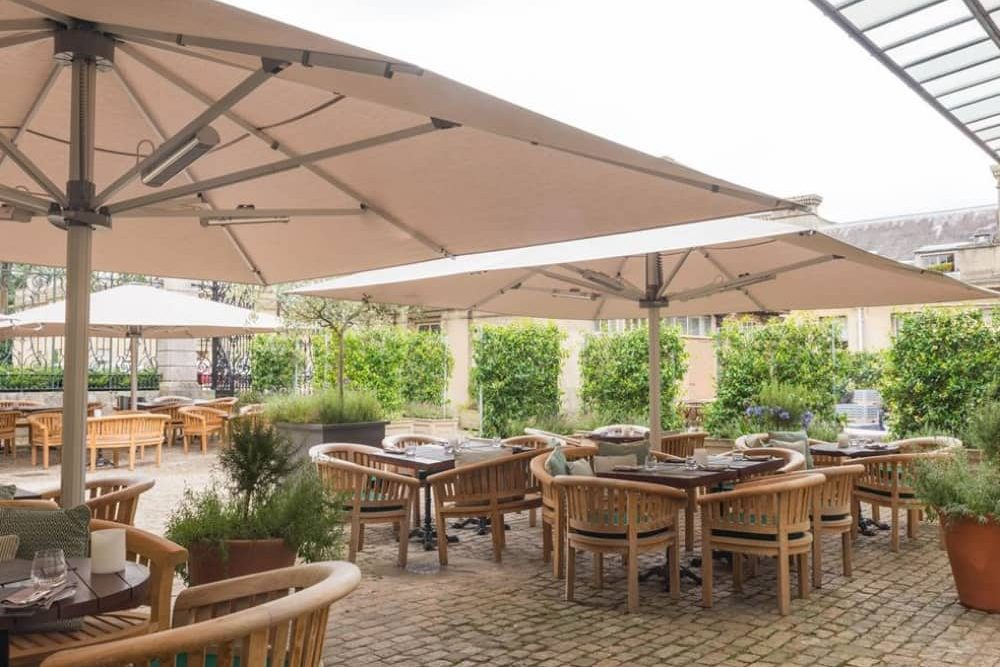Astor Grill Clivden House Hotel sun terrace with large cream parasols wooden furniture and pot plants