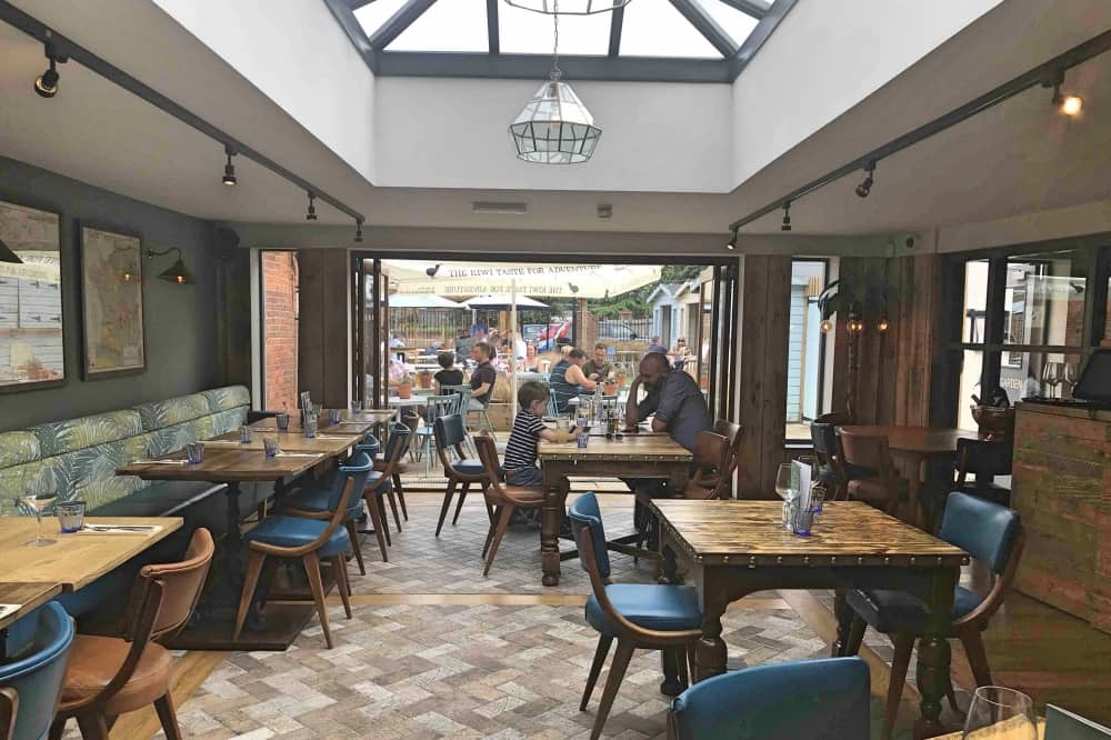 The Dolphin newbury Berkshire light restaurant wooden tables parquet floor roof lantern bi fold doors palm print seating and brass palm tree floor lamp