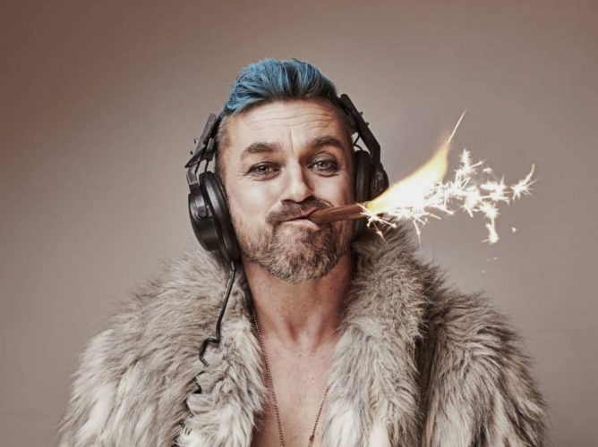 Comedian Eddie Summer Rocket Fuel Man wearing fur coat headphones with sparkle in his mouth