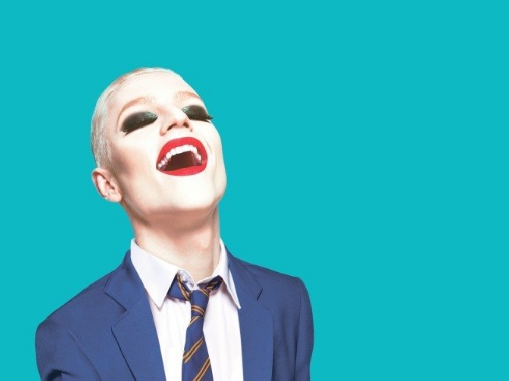 Everybody's talking about Jamie musical suited man in full drag make up red lips fake lashes and blue suit