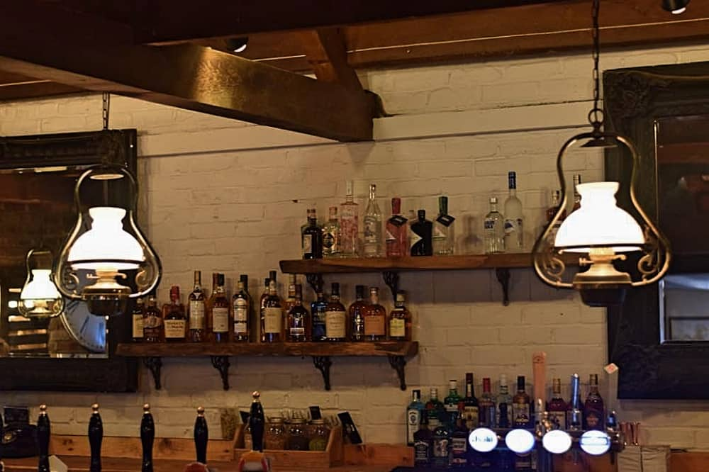 Jolly Woodman Burnham Slough hanging oil lamps over the bar white painted brick wall and open rustic shelve with bottles of spirits