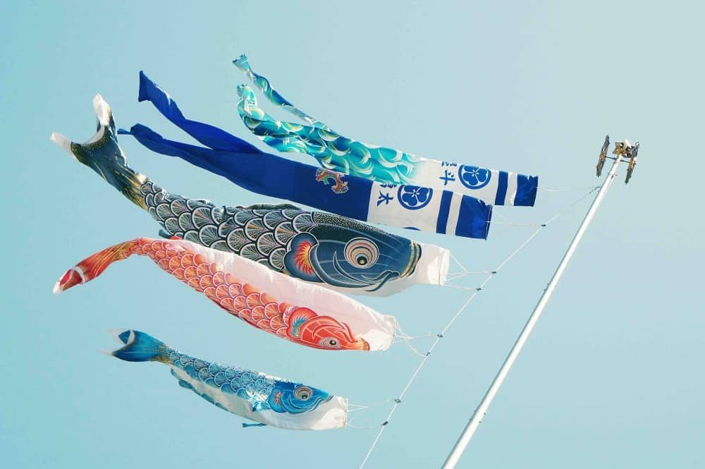 Fish kits on a boat mast flying in blue skies
