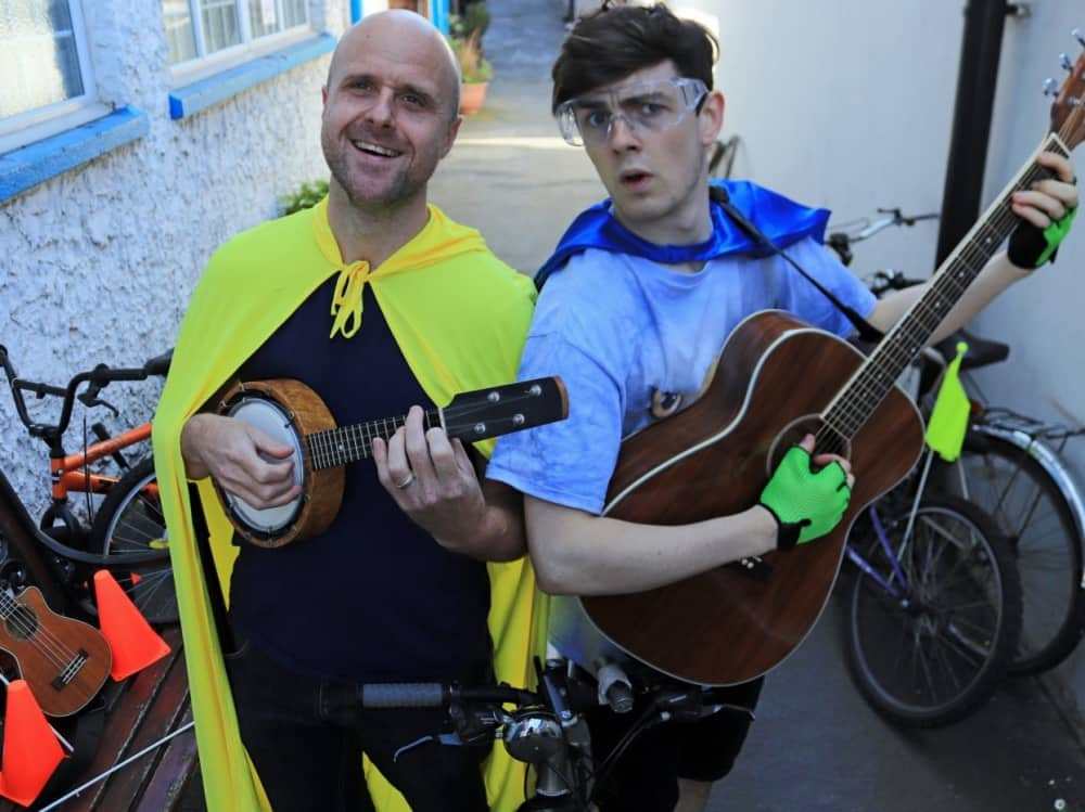 Reading Festival Bicycle-Boy – 2 men wearing a yellow and blue cape playing guitars surrounded by bicycles
