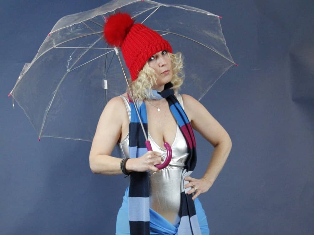 Reading Fringe Fetsival Stand-Up Weather Girl blonde woman holding umbrella wearing read bobble hat and satin slip and a scarf