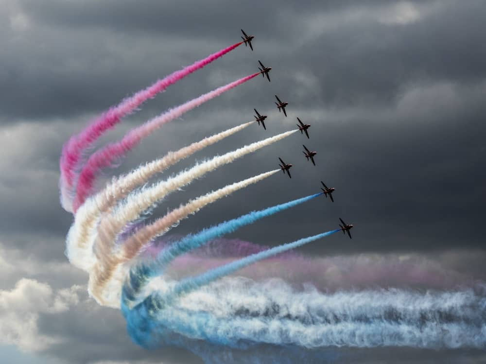RAF100 flypast read arrows in formation red white and blue smoke in stormy skies