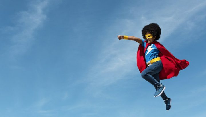 Boy superman pose leaping into the sky wearing red cape and yellow mask jeans