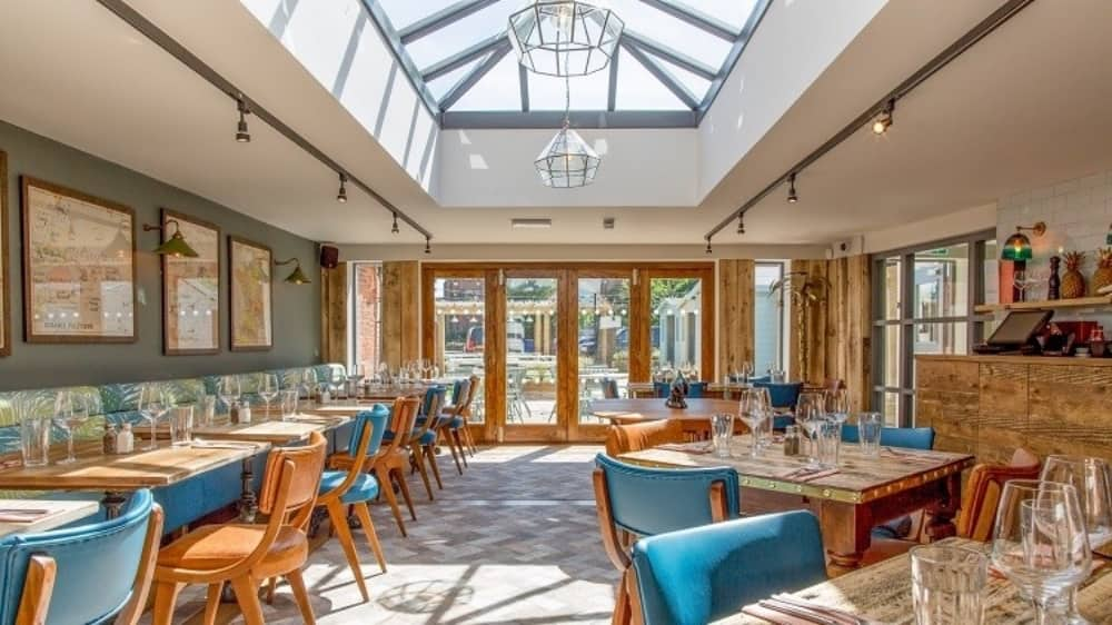 the Dolphin Pub Newbury Berkshire Light bright restaurant palm print seating, wooden tables tan and teal chairs wooden floors brass palm floor lamps and bi folding doors to the garden