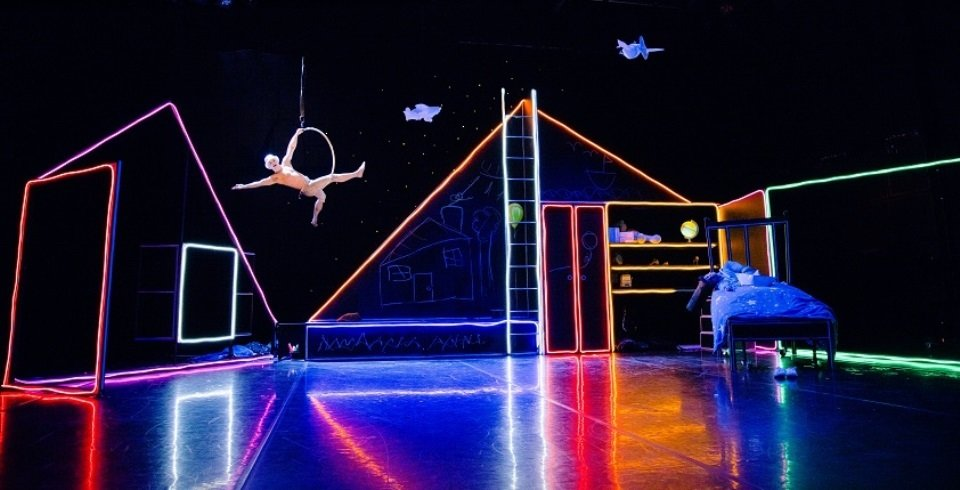 Neon lit staging and circus performers What The Moon Saw Corn Exchange newbury