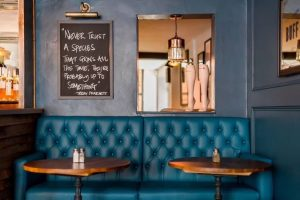 The Dolphin Pub Newbury Berkshire Teal leather banquette, dark blu walls chalk board and vintage stocking props