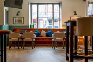 The Dolphin Pub Newbury Berkshire orange velvet sofa cushions wooden floor and mix and match wooden tables and chairs