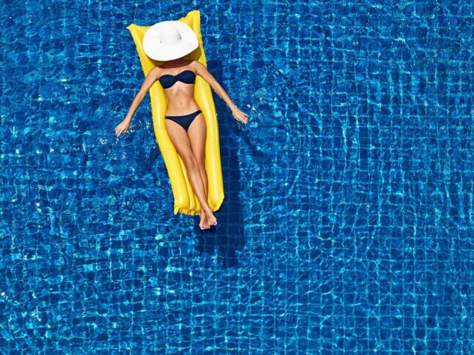 Woman wearing white hat on yellow lido in pool
