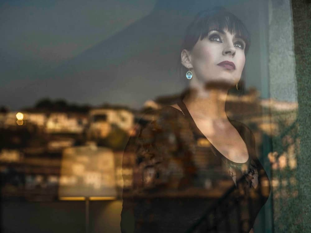 Portugese singer Claudia Aurora staring through the window to the white rendered buildings of a portuguese town