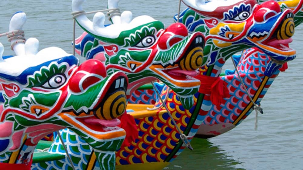 Colourful painted dragon heads at front of boat racing in Dragon festival reading Berkshire