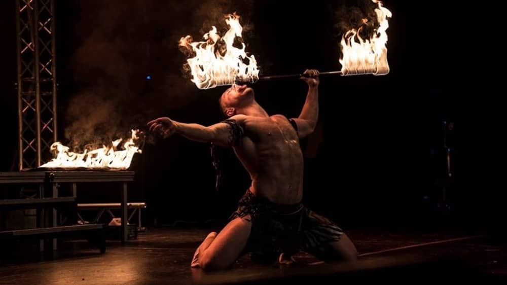 Forbidden nights sexy circus man on knees wearing black pants eating fire