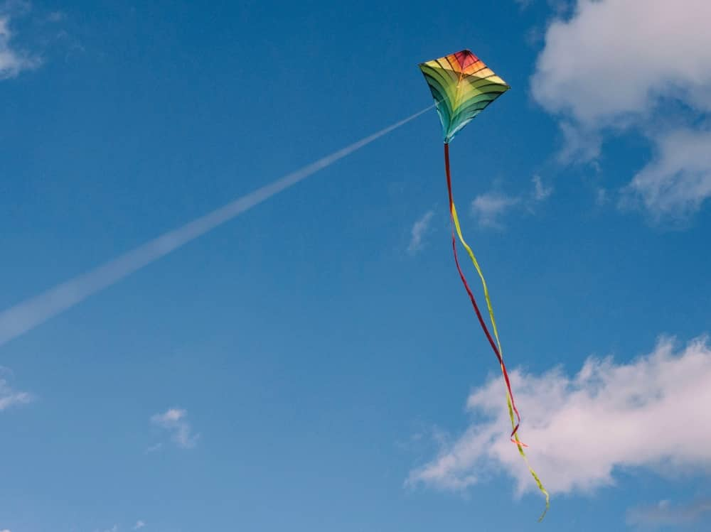 Multi coloured kite flying in blue sky with ribbon tail