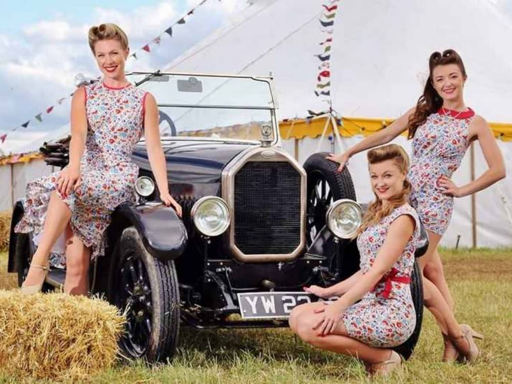 Retro Festival Newbury west berkshire three girls in floral print dress sat on an old car surrounded by hay bales and a bell tent