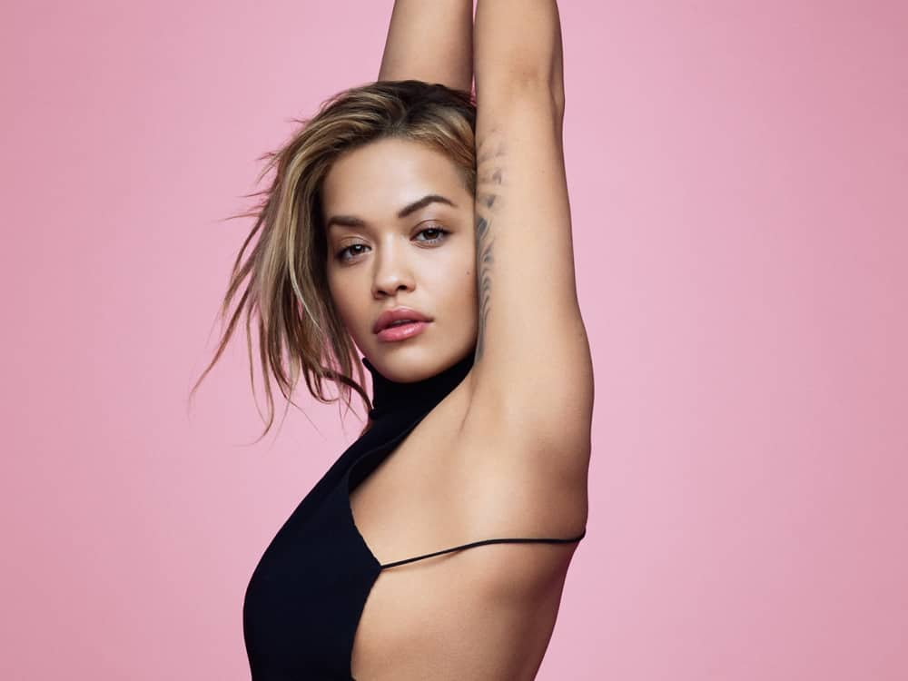 British singer Rota Ora bobbed hair black top arms stretched above her head on pink background