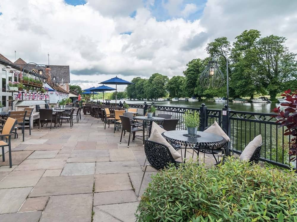Swan at Pangbourne Berkshire riverside outdoor terrace paved tables and chairs boats