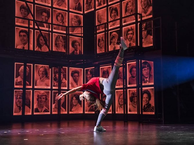 Fam The Musical UK tour red lit walls of black and white photos dancer leaning back into a high kick