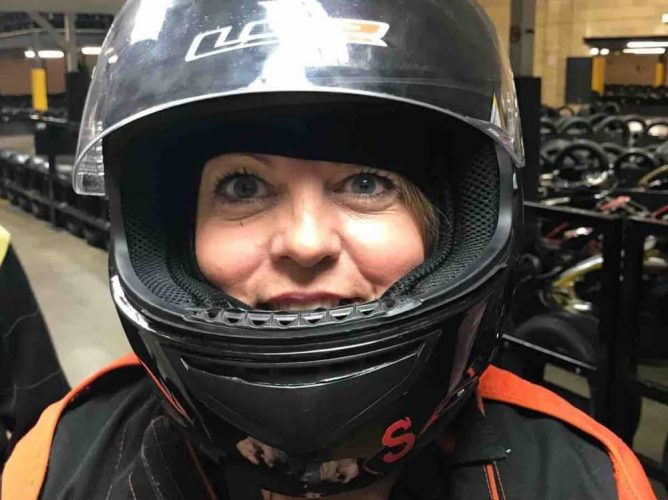 Muddy Stilettos Berkshire editor Rachel Jane in black race suit and helmet at Absolutely Karting Maidenhead