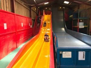 Bucklebury Farm Park indoor slides – yellow and red bumpy slide and dark blue drop slide