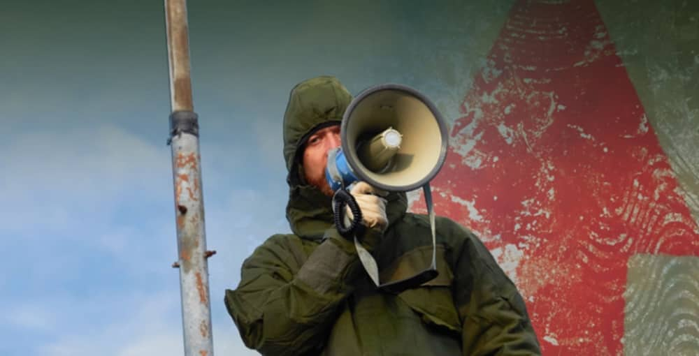 Greenham Common Control Tower immersive theatre event man in hooded jacked with loud hailer