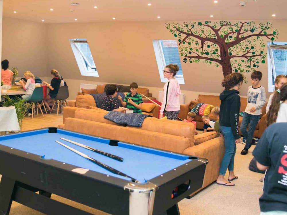 Eagle House School Sandhurst Berkshire boarders social area pool table squishy tan sofas eames style chair and cool artwork