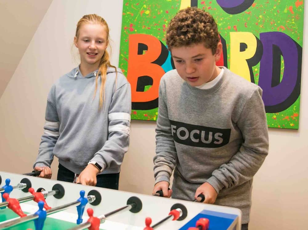 Eagle House Prep school Berkshire Girl and boy playing table football in common room with urban artwork on walls