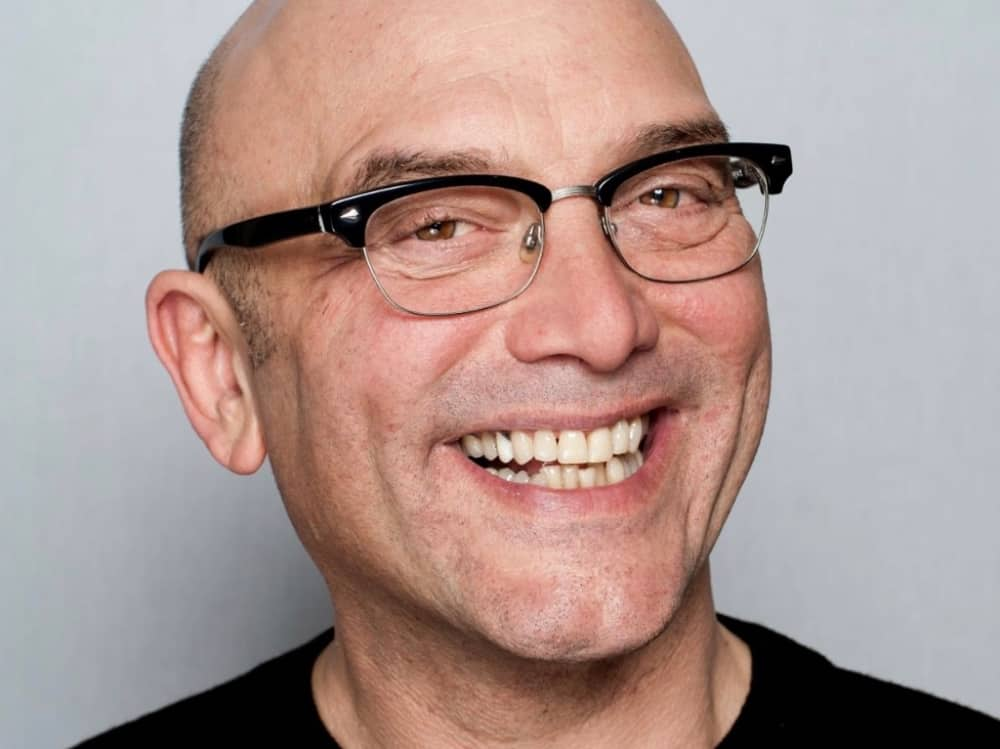 Masterchef UK TV presenter Gregg Wallace bald, black t shirt half framed glasses