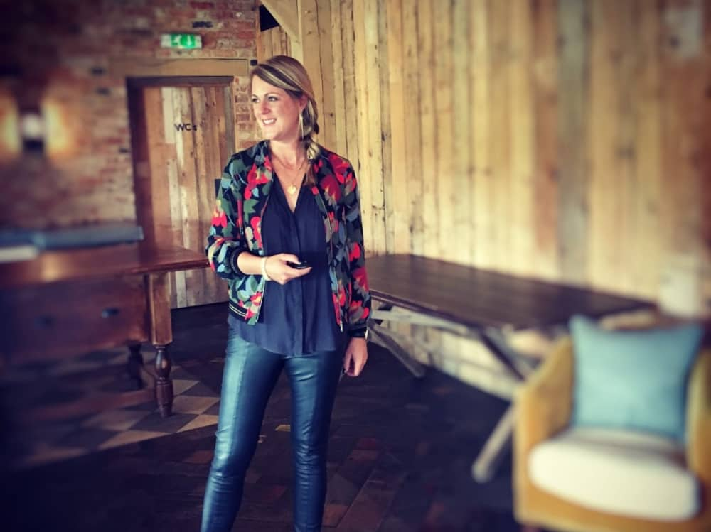 Stylist Kate Evans at Jax Jeans Hungerford Berkshire wearing jeans black top and floral bomber jacket in rustic wood panelled room