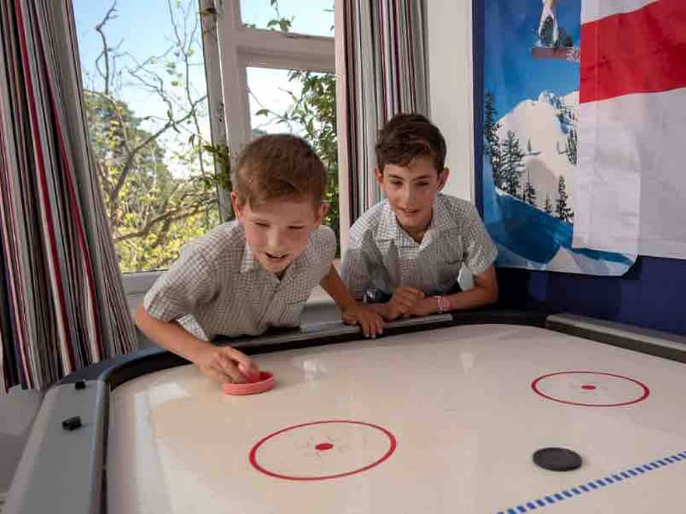 Lambrook School boys boarding house two boys playing air hockey with england flag on the wall