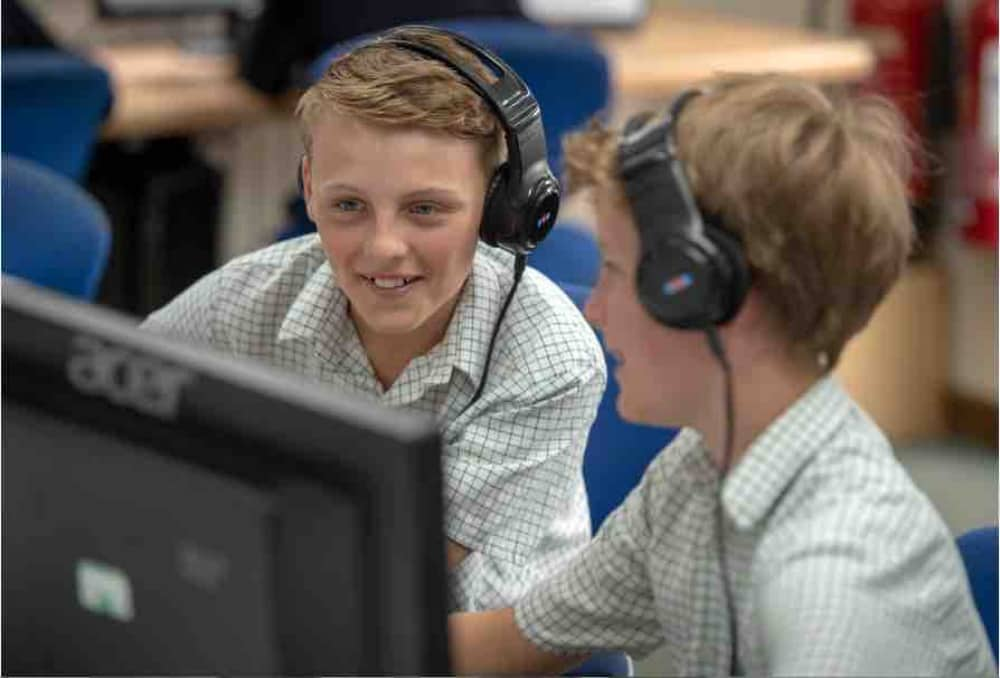 Lambrook School two boys wearing headphone and computers in the IT suite at Lambrook School Berkshire