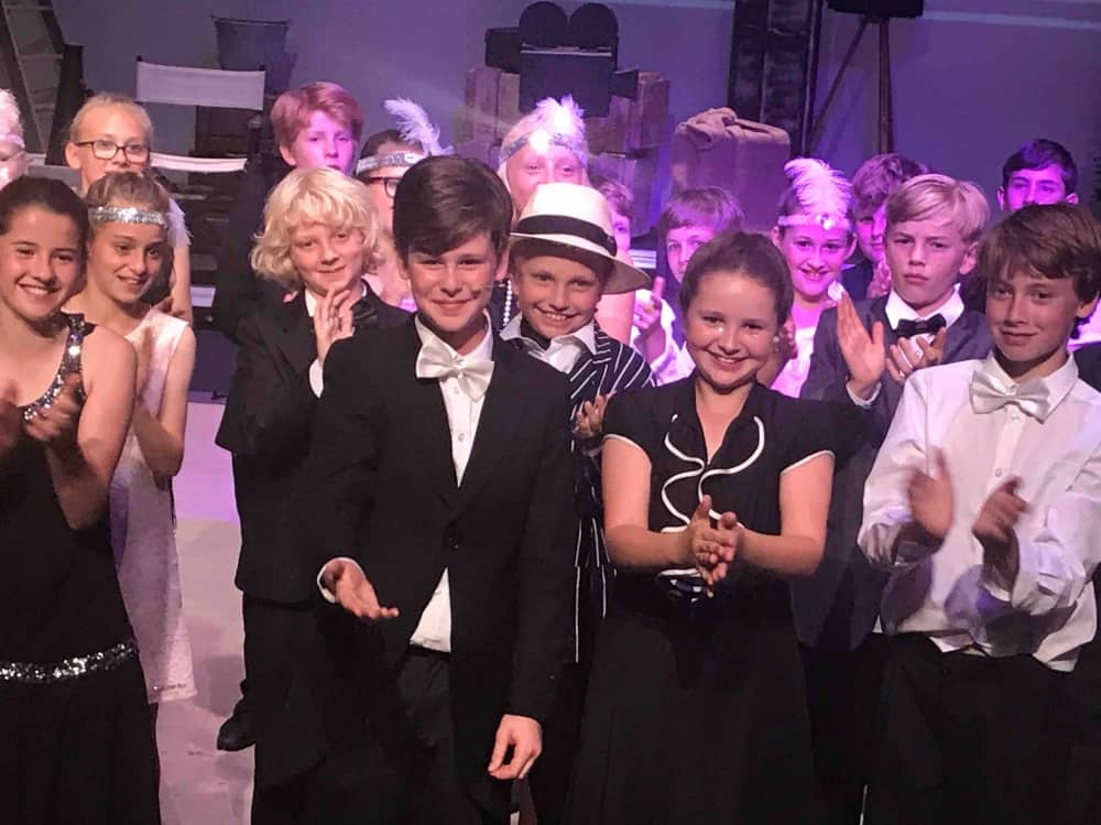 Lambrook School musical cast of boys and girls wearing black tie, fedoras and pearls