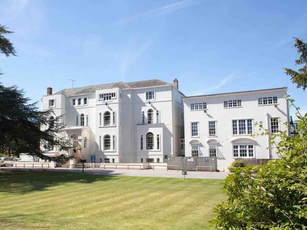 Lambrook Prep School Berkshire Huge white mansion house with front lawn framed by mature trees blue sky