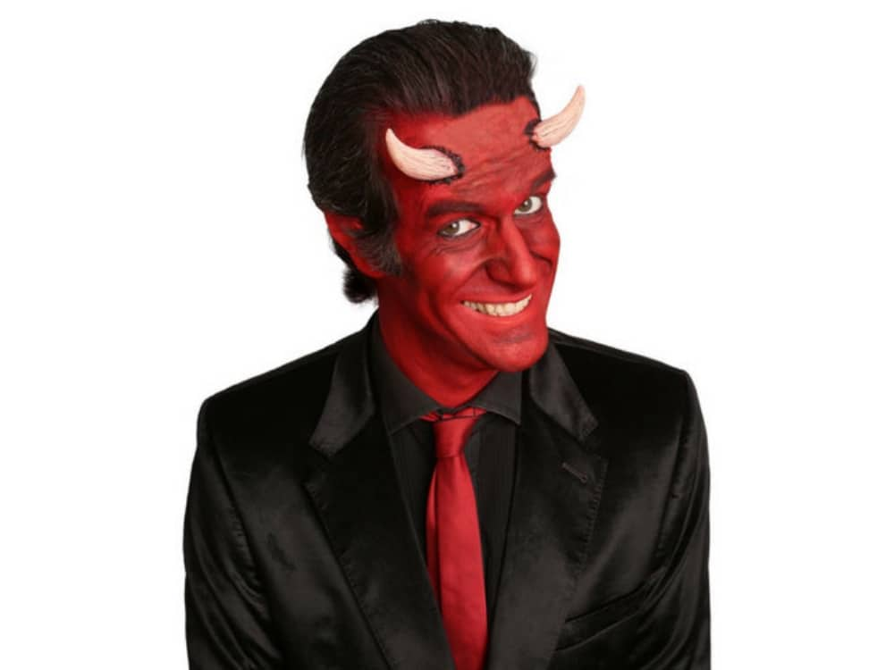 Comedian Marcus Bridgstock dressed in black suit red tie with devil horns and a painted red face