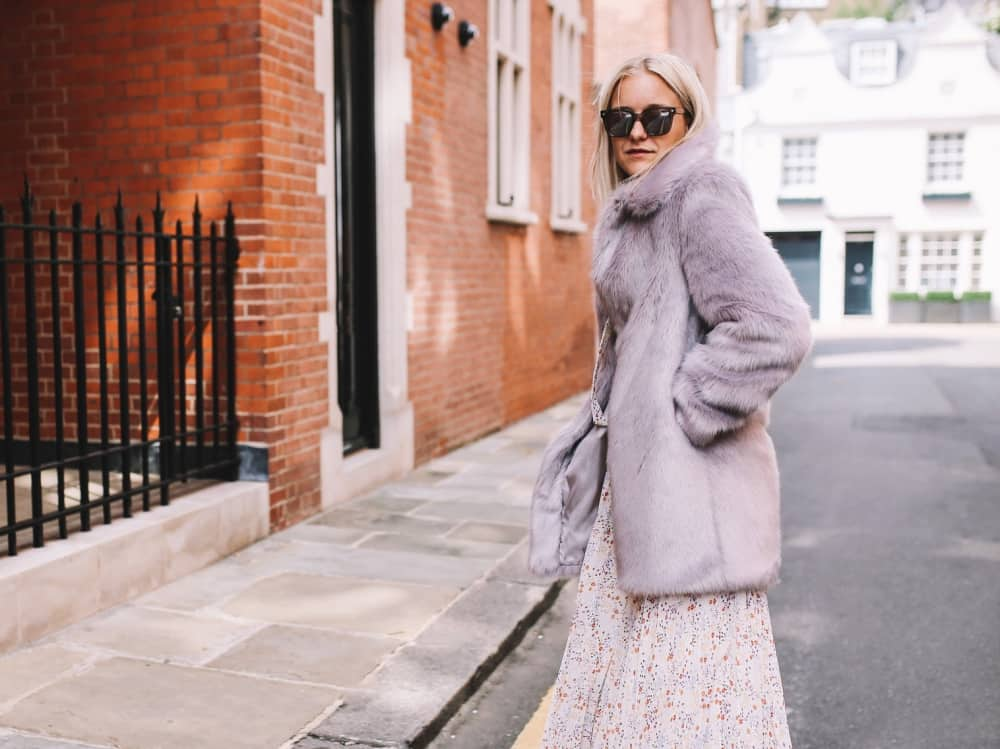 Blonde woman wearing lilac Miranda Dunn London faux fur midi coat on London street