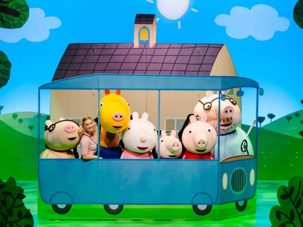 Peppa Pig and friends live theatre show travelling in the blue bus past a house