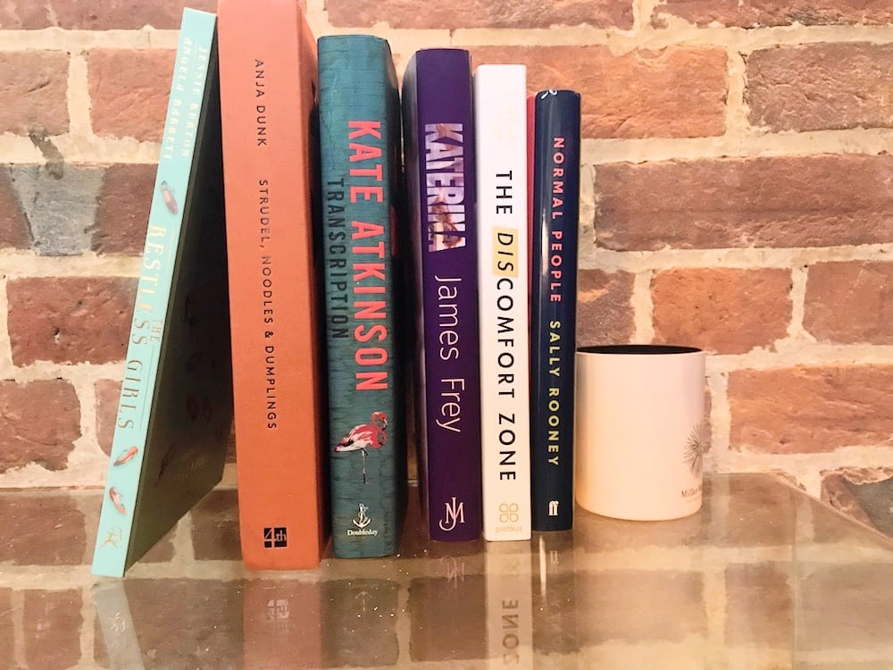 september new book releases stood up against each other against a brick wall