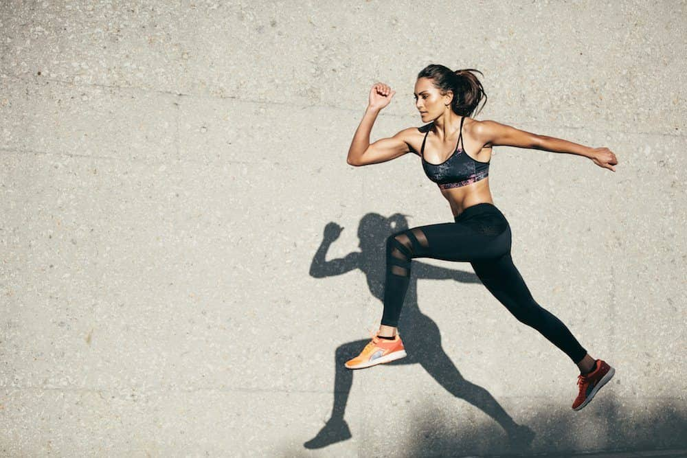 Woman leaping in running leggings and bra top past a conc rate wall