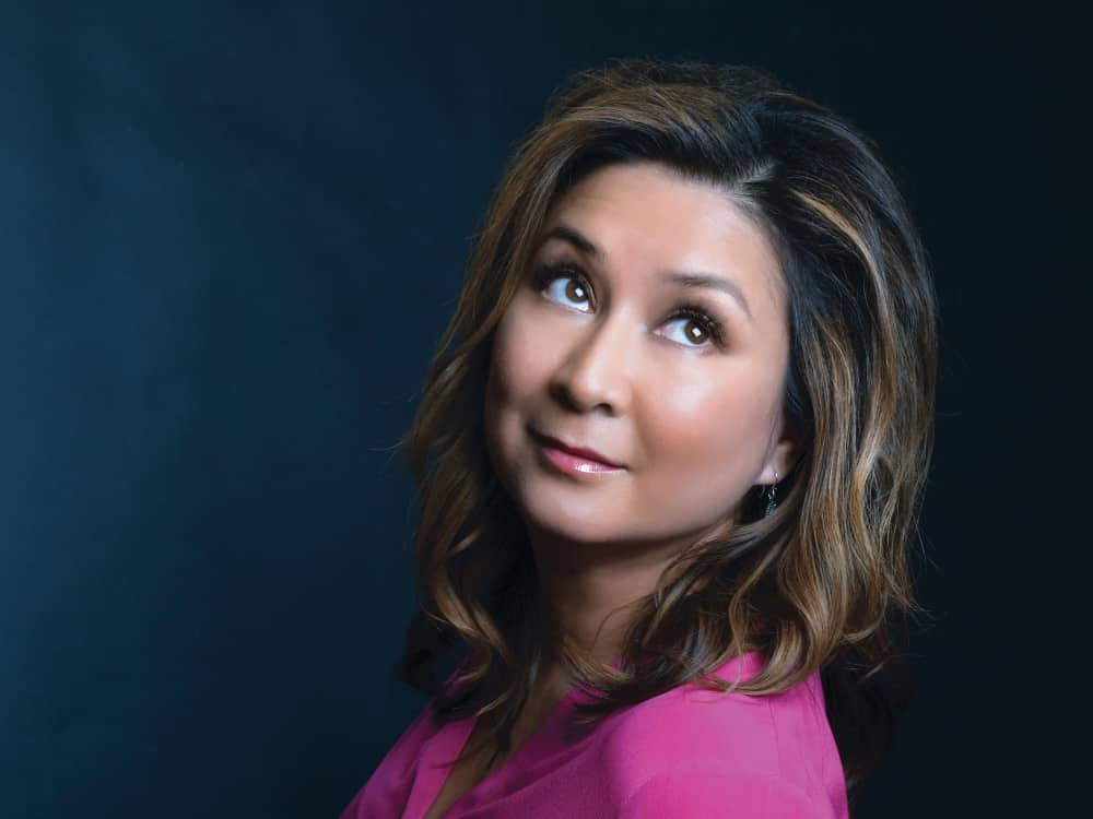 Political pundit Ayesha Hazarika brown hair pink top navy background