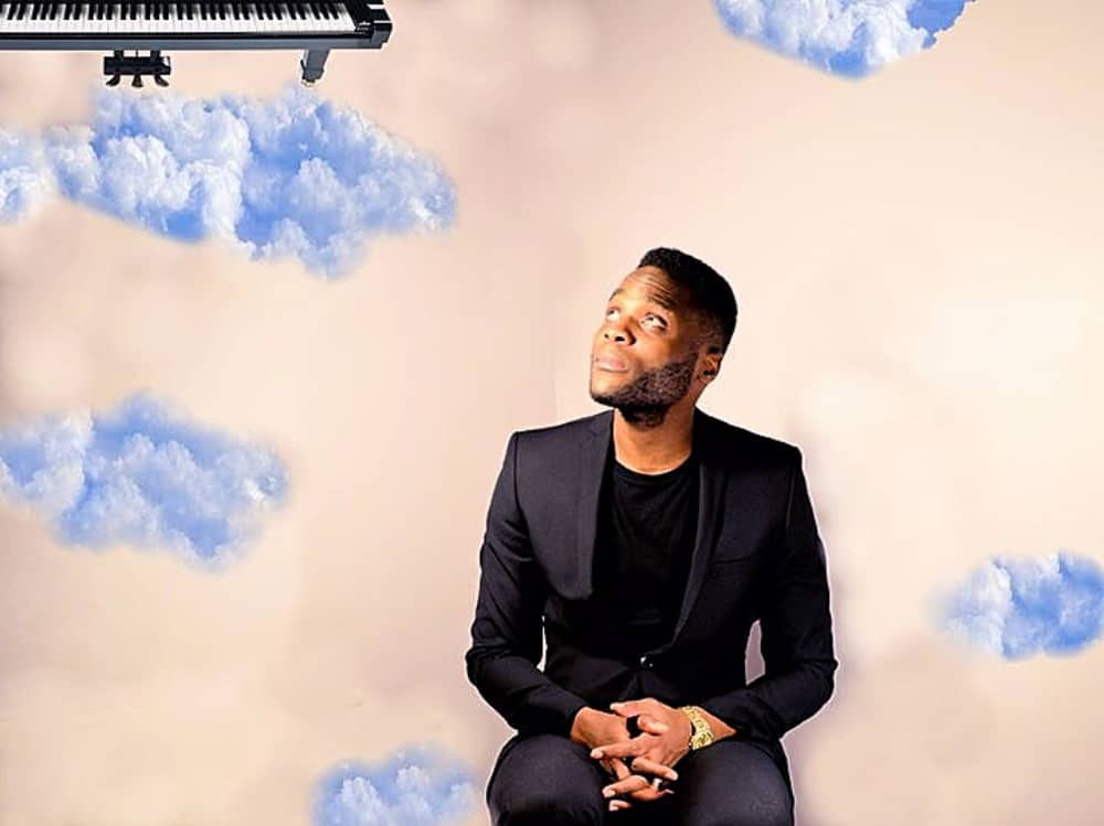 Soul singer BR James black suit and short cloud background piano in corner