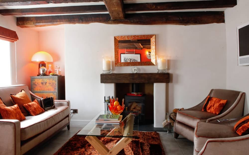 Bray House Bray Cottages Berkshire mink velvet chair and sofa exposed beams fire pace glass coffee table and orange cushions